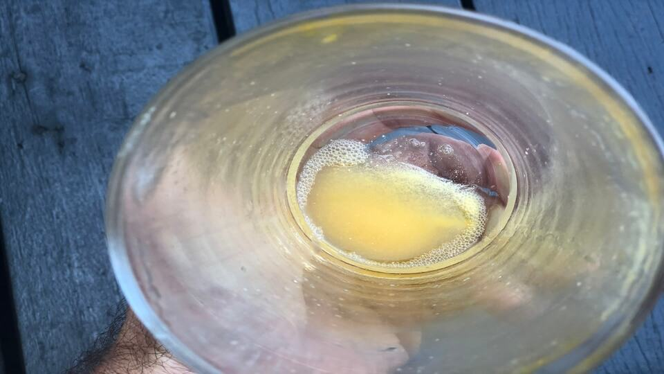 Undissolved powder at the bottom of a glass of Zipfizz orange soda
