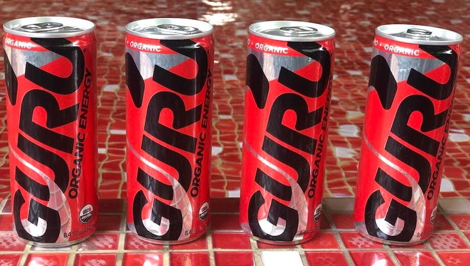 guru energy drink cans against a red background
