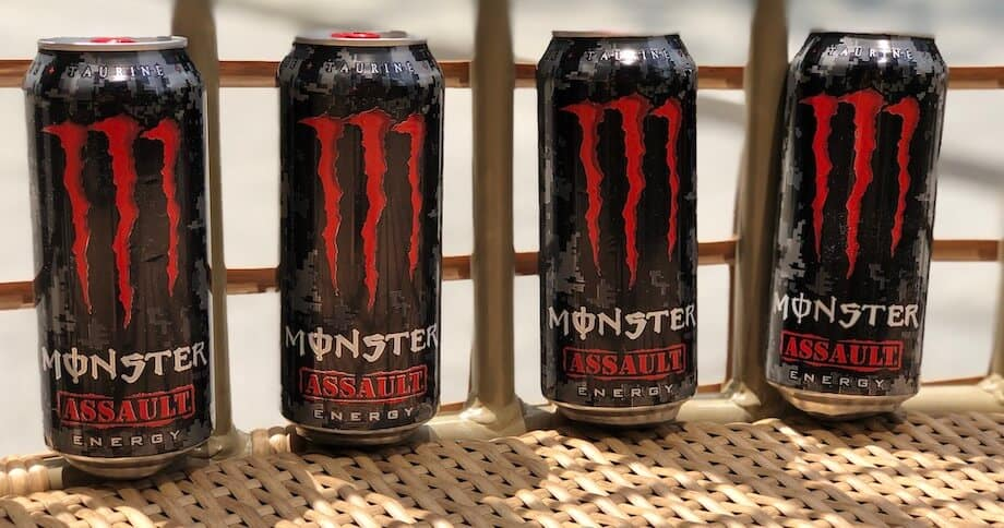 4 Monster Assault cans against bars