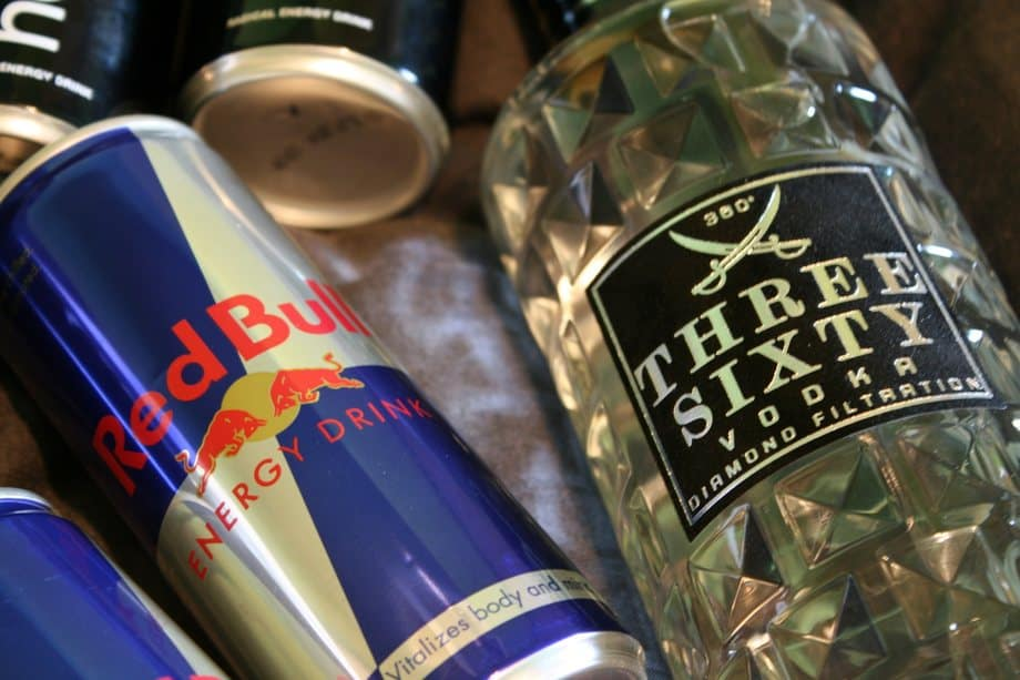 A can of Red Bull energy drink next to a bottle of vodka