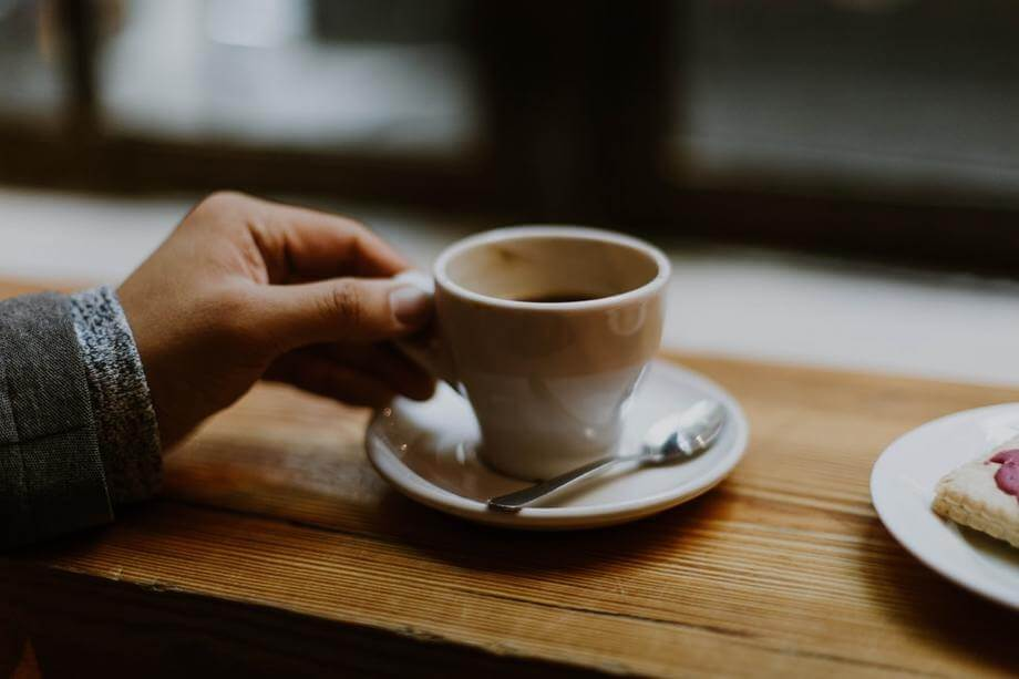 a person with hand on a cup of coffee or tea