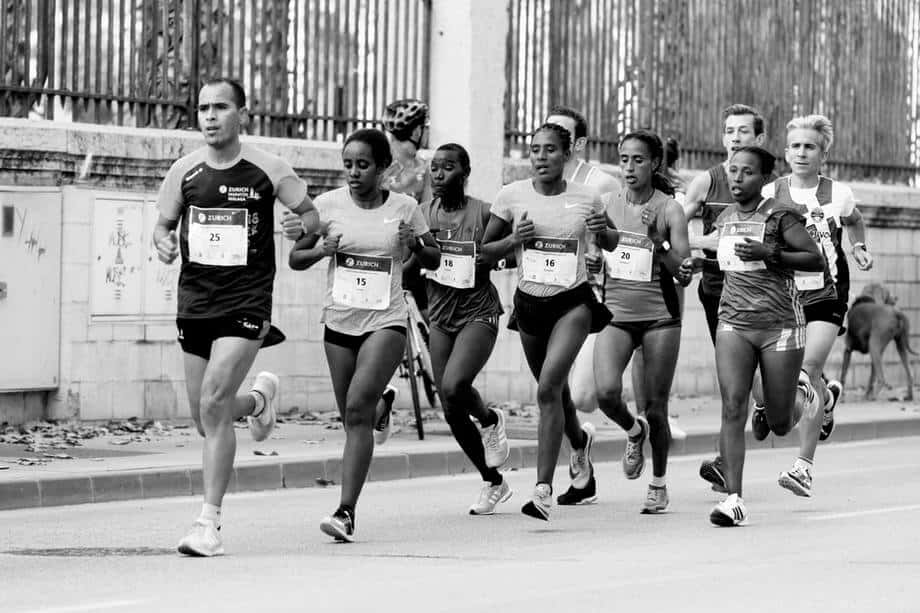 a group of marathon runners training, photo in black and white