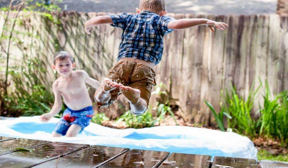 a child jumping into a backyard pool while another child looks on from inside the pool