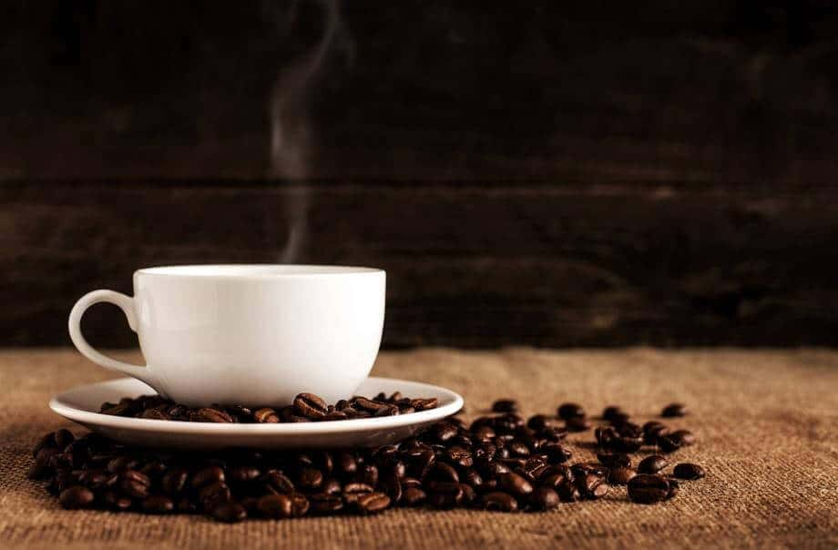 A brewing cup of coffee with coffee beans all around it