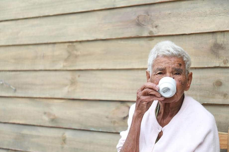 elderly man drinking coffee from a small coffee cup