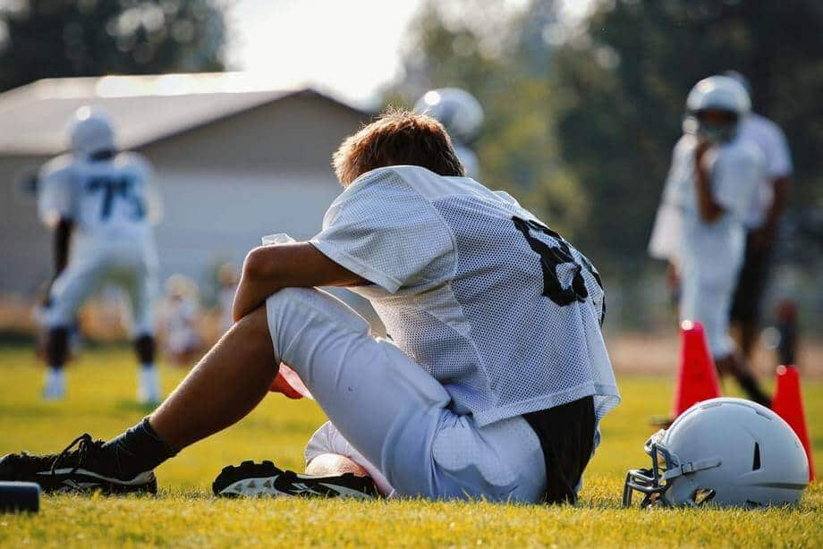 football player in white jersey resting on the field