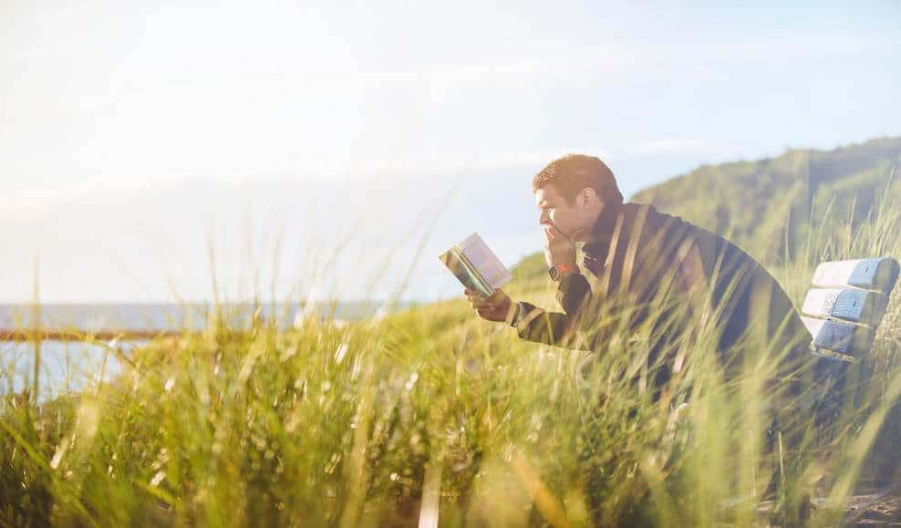 guy concentrating on reading in a meadow