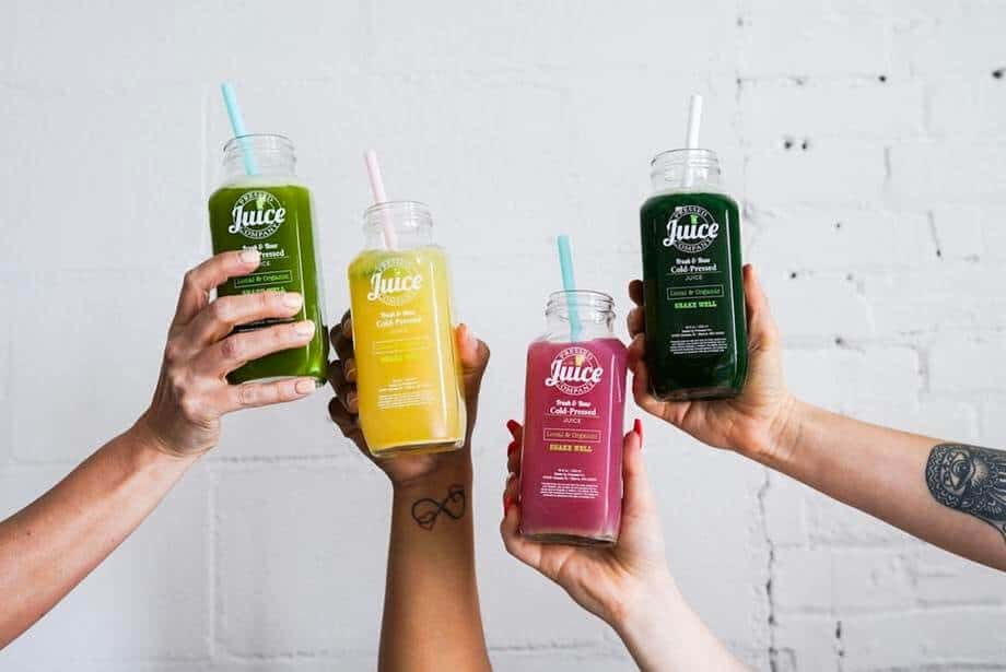 4 hands holding colorful juices