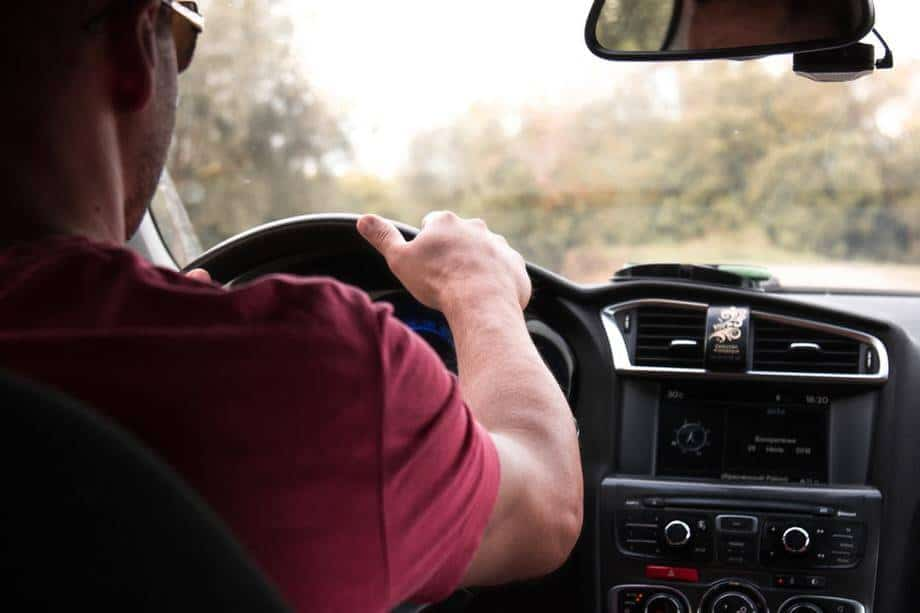 a man in red shirt driving a car