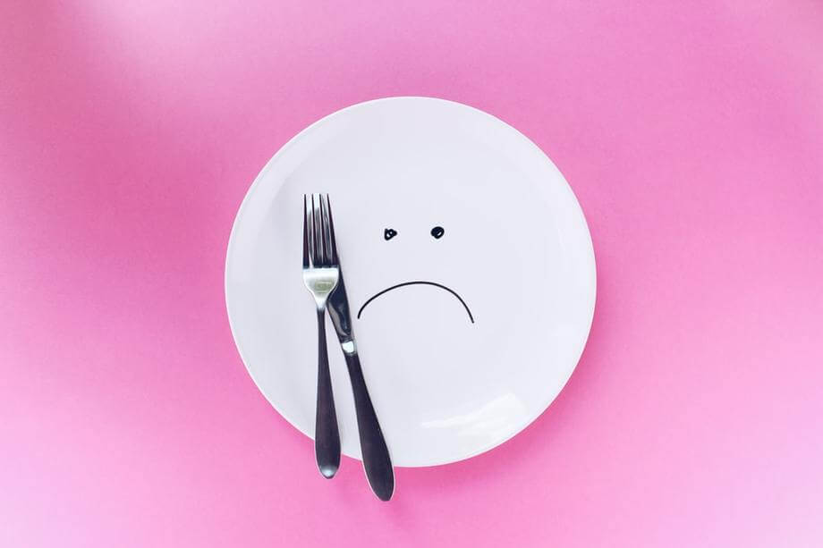 a plate with a sad face and fork and knife