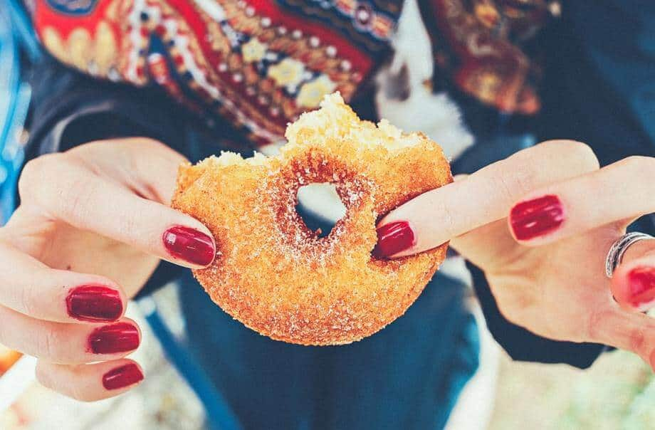 a women holding a sugary sweet donut