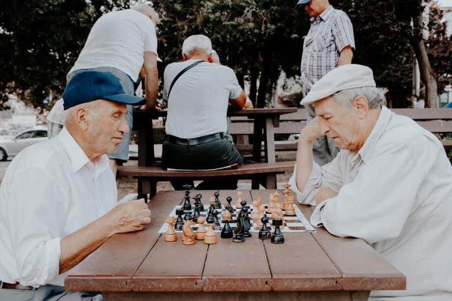 two elderly man playing chess in the park