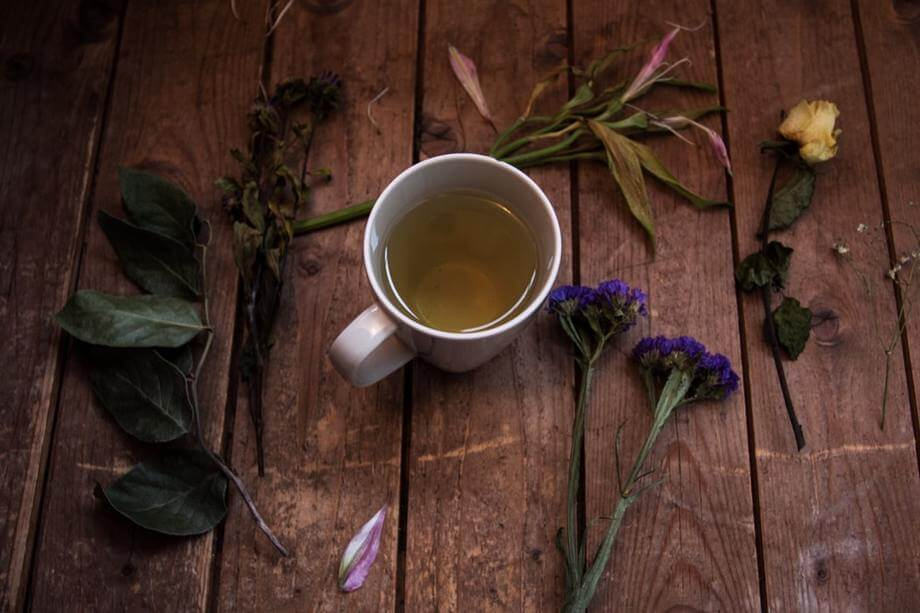 a cup of green tea on a table with flowers