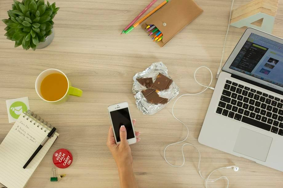 a work desk with a laptop, a cup of coffee, an iphone and chocolates