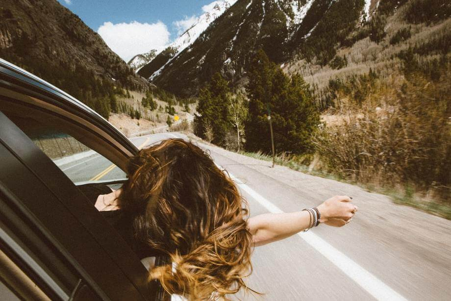 woman enjoying drive with head out window