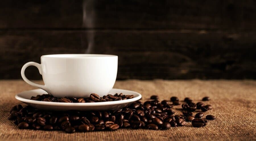 A cup of coffee with coffee beans around.