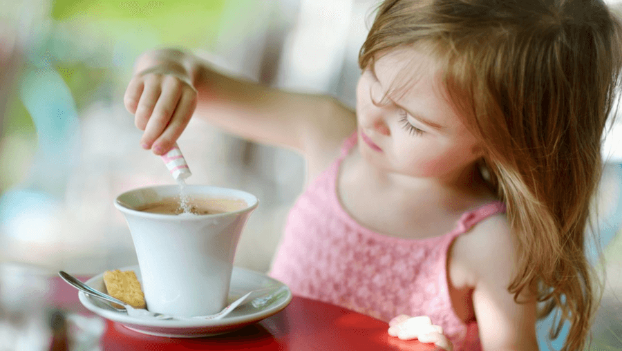 A young girl making a cup of coffee