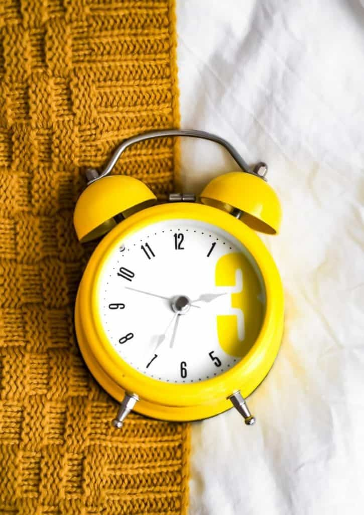 A yellow alarm clock on bed