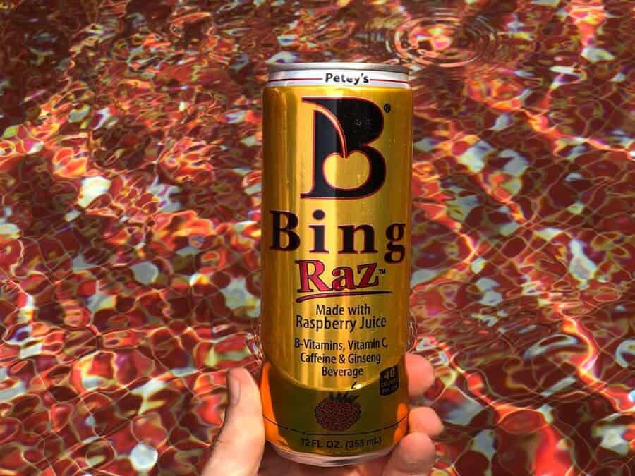 a can of Bing energy drink held by a hand in water