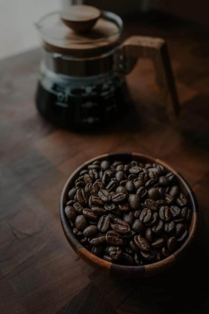 Coffee bean in a bowl and a pot of coffee