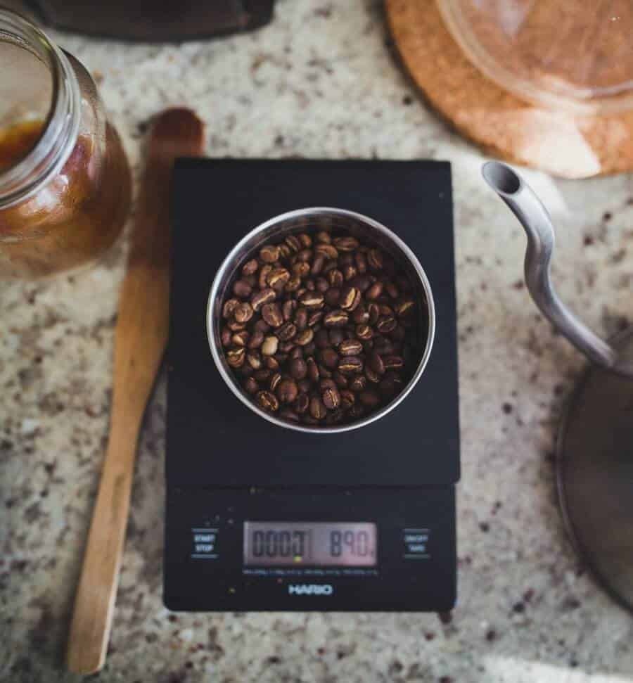 A bowl of coffee beans on a weighing scale