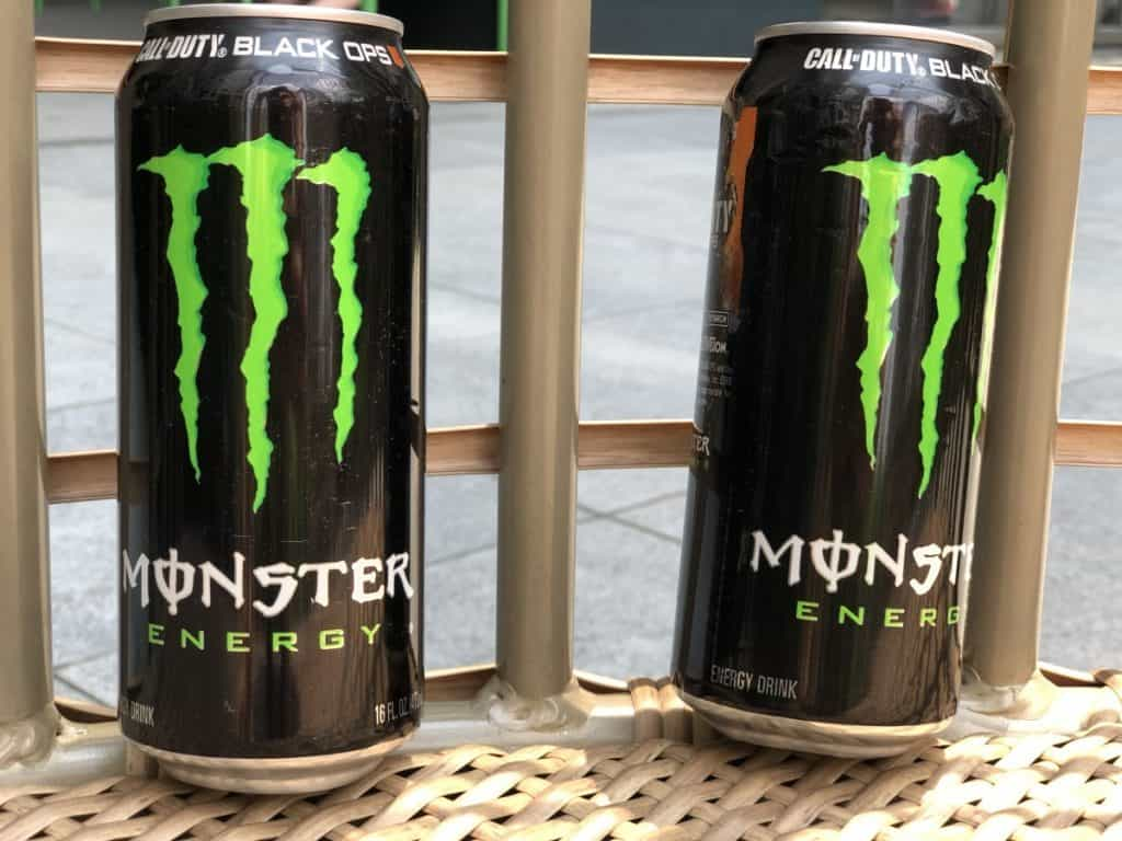 2 cans of Monster energy drink sitting next to each other