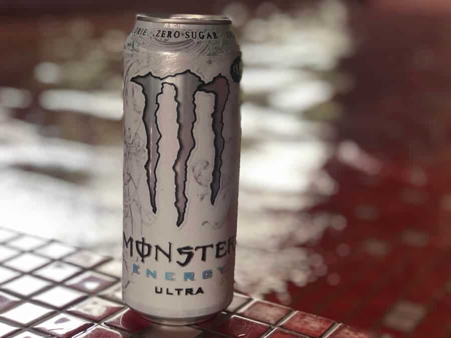 A can of Monster energy drink i front of a pool