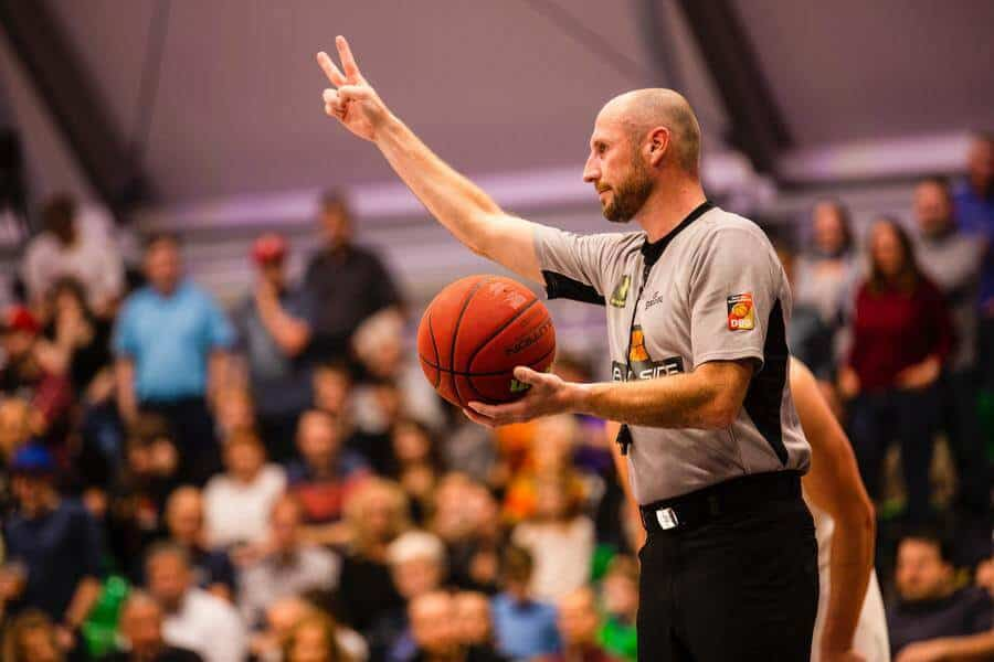 An aged referee holding a basketball in a tournament