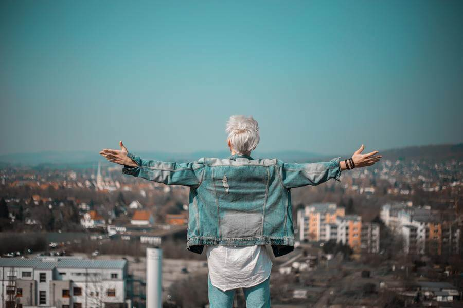 Old man standing on a ledge before a view of the city