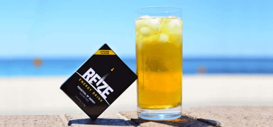 A REIZE sachet and a glass of REIZE drink on a beach