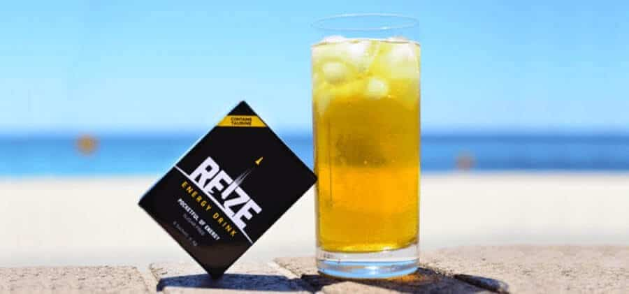A sachet of REIZE energy drink powder and a glass of the ready-made drink.