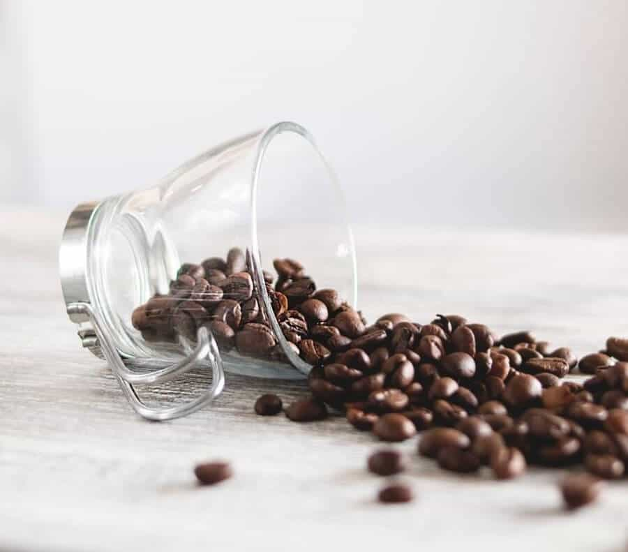 Glass cup lying on the side with coffee beans spilling out