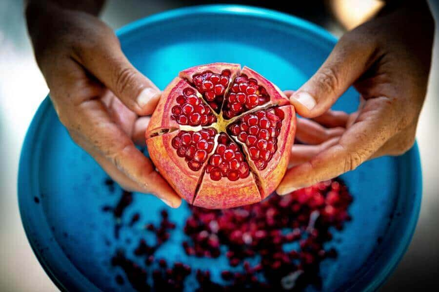 a hand holding up a cut-open pomegranate
