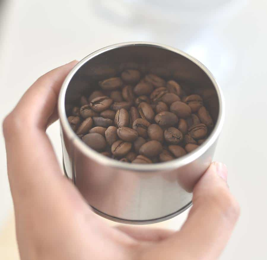 Hand holding a small container of coffee beans