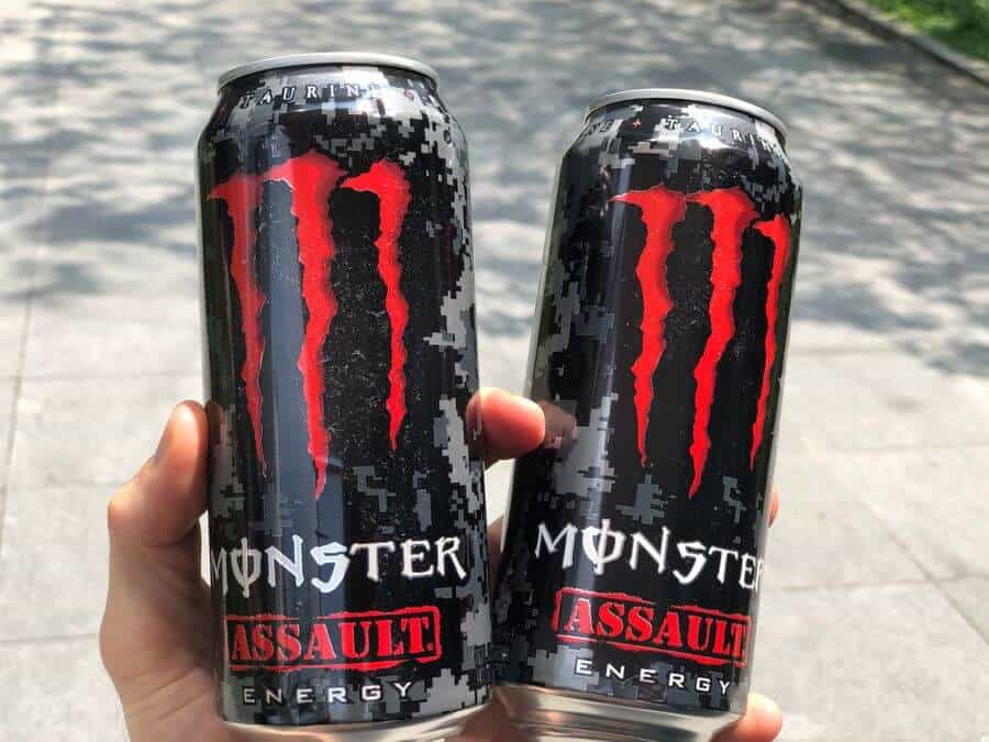 Two cans of Monster Assault in a hand