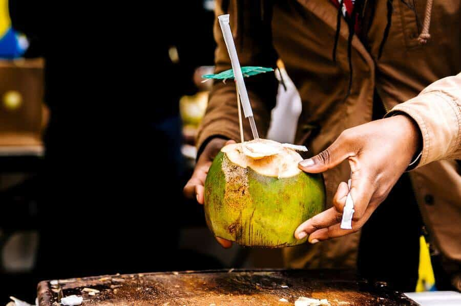 A person holding a coconut drink