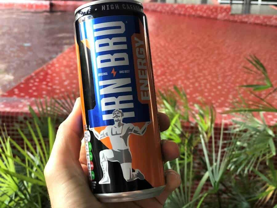 A handheld can of Irn-Bru Energy with green foliage in the background.