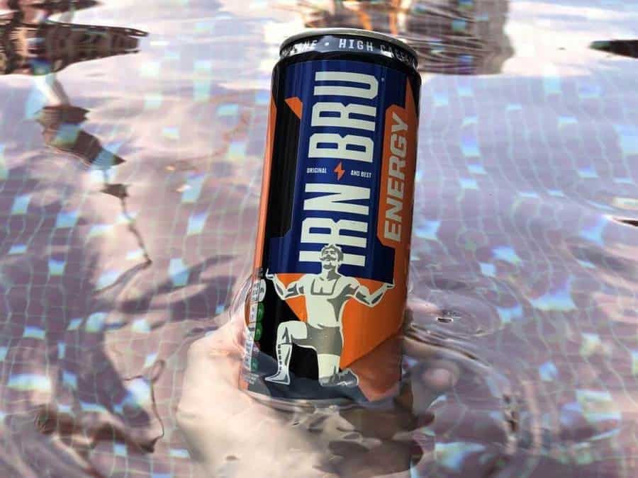 A can of Irn-Bru Energy that's partially submerged in water.
