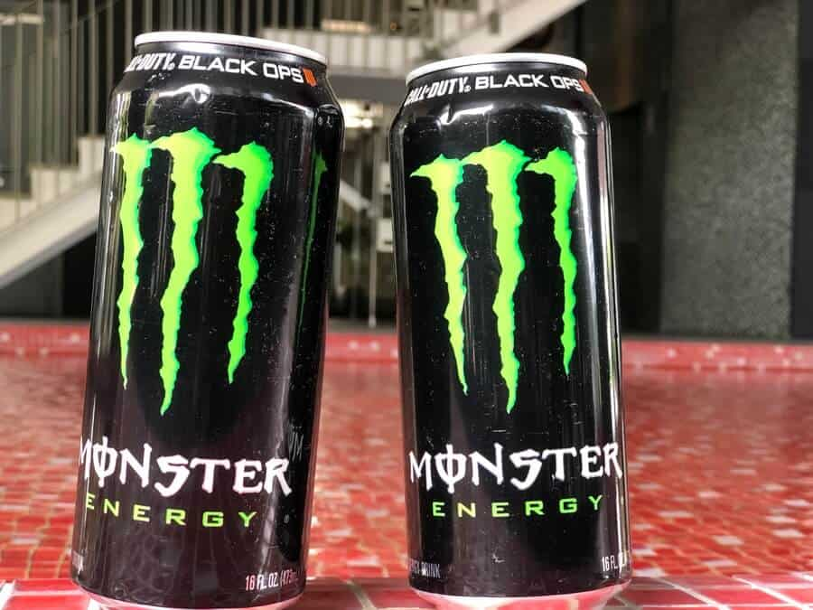 Two cans of Monster energy drink arranged side by side.