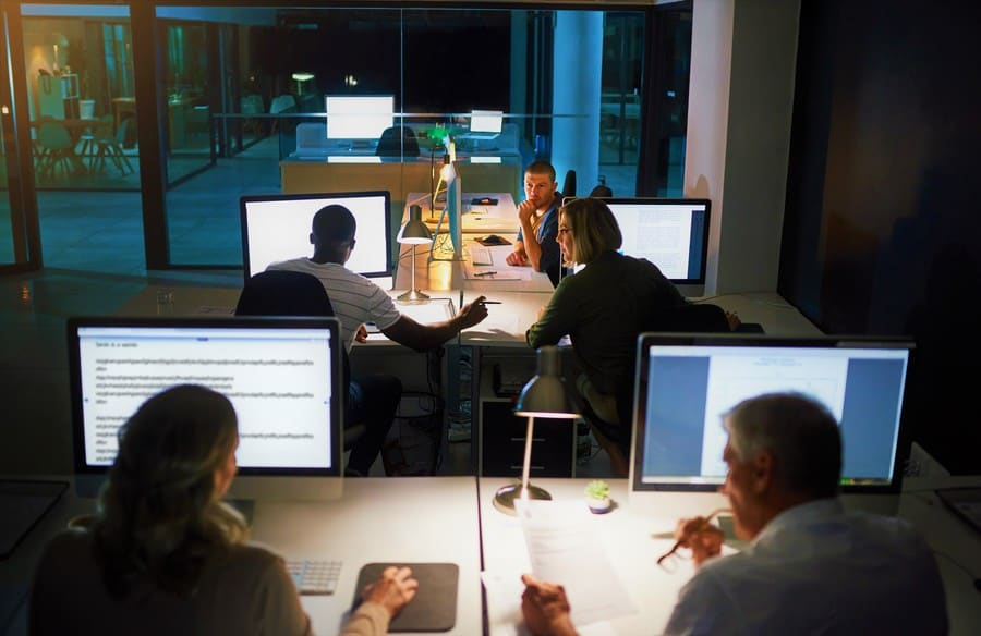 People working late in an office, discussing with each other.
