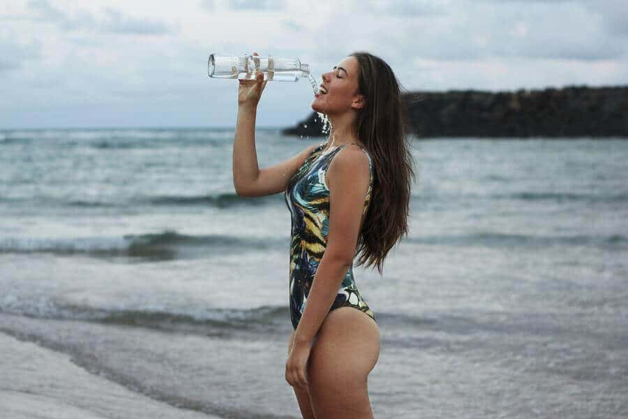 Woman in swimsuit by the sea drinking a bottle of water