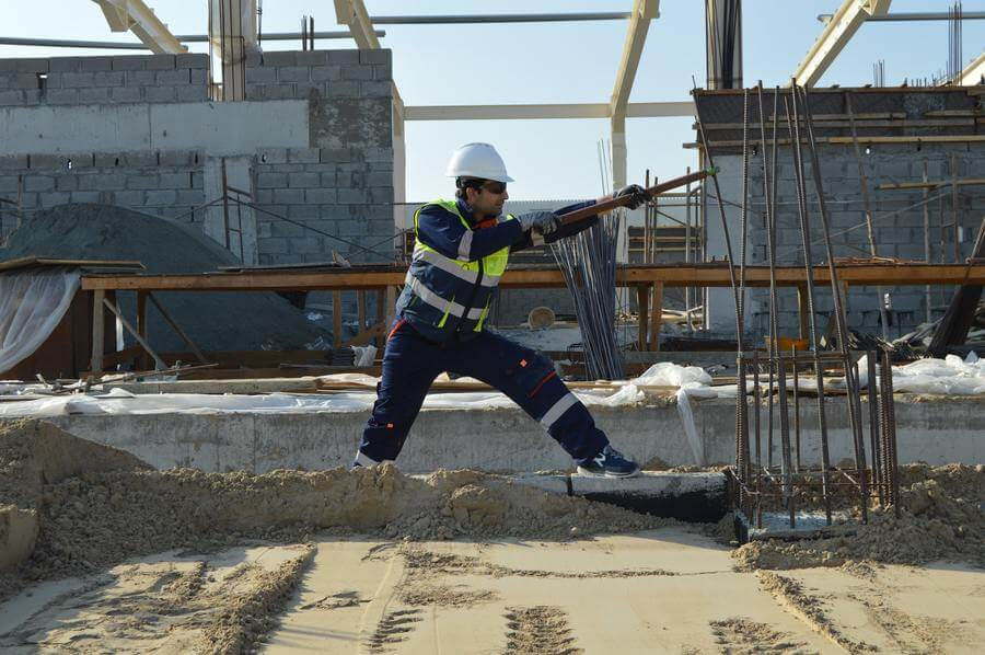 A construction worker pulling on some metal rods at work