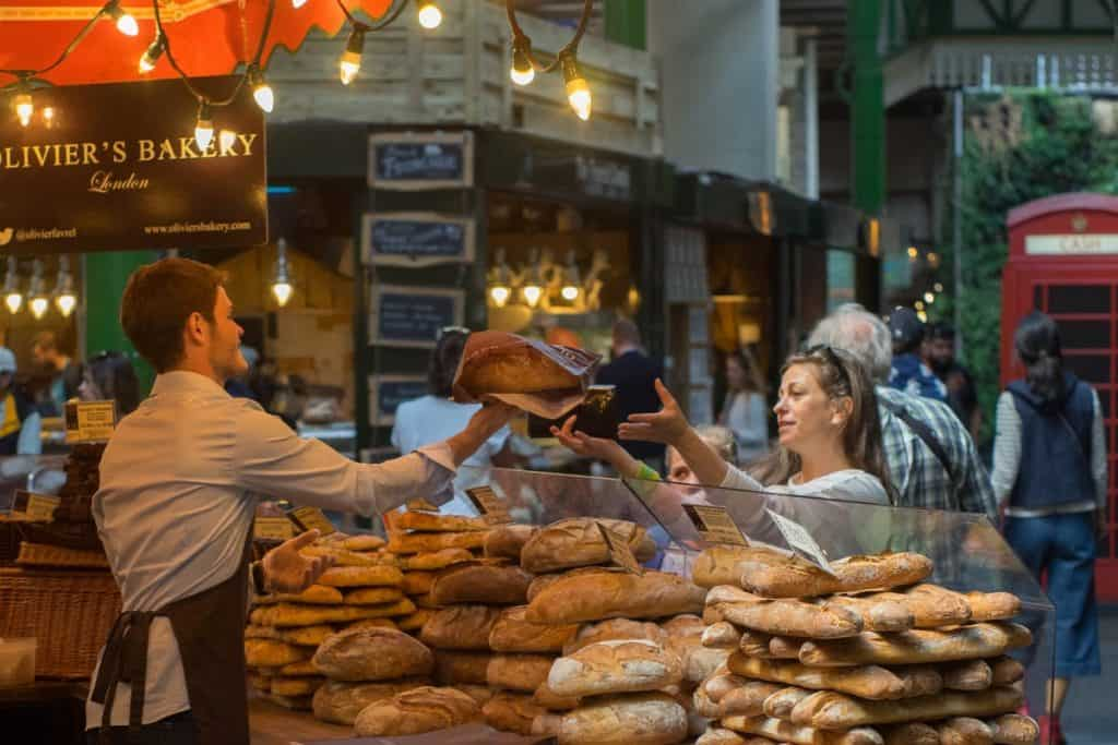 Woman buying bread from a shop