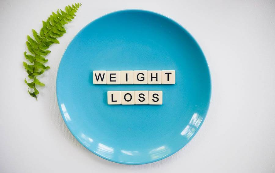 "Scrabble tiles spelling ""WEIGHT LOSS"" on a blue plate."