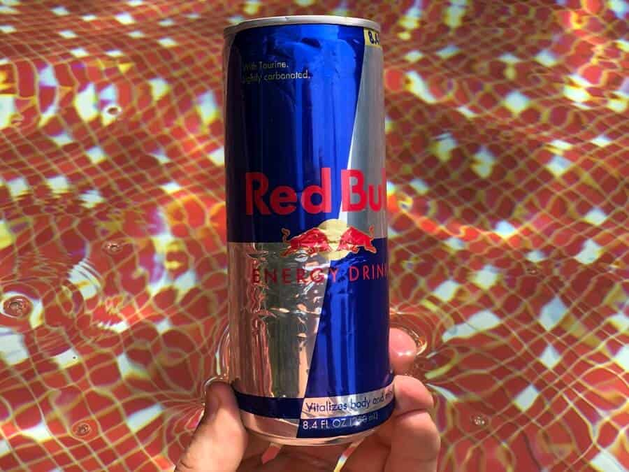 a handheld can of Red Bull energy drink.