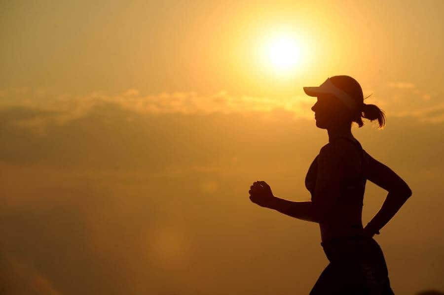 A silhouette of a girl wearing athletic attire running with a dusky background and orange sun behind her