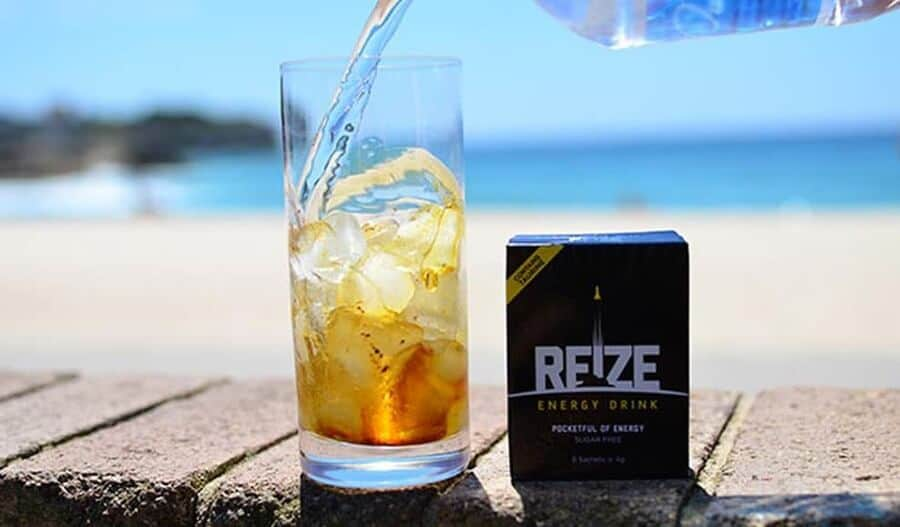 """A glass half-filled with ice cubes is being filled with water from a bottle. The colour of the drink in the glass is yellowish-brown, and gets lighter from bottom up. A small box labeled """"REIZE ENERGY DRINK"""" is next to it. A blurred beach background."""