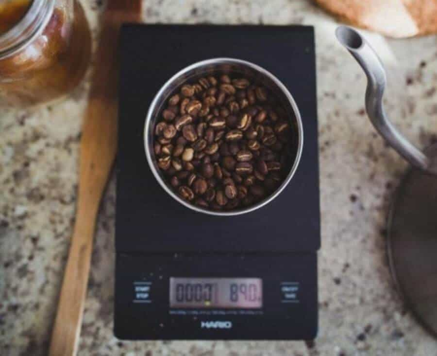 coffee beans being weighed on a digital scale on a grainy countertop