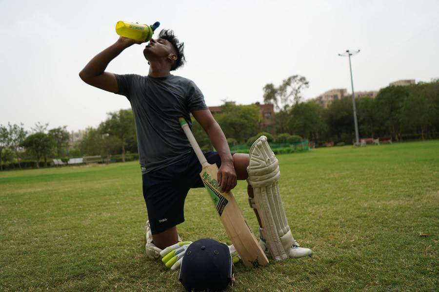 A cricket player in sports attire and leg guard kneels on one leg with his cricket bat against his torso and drinks from a yellow bottle with his head tilted back. Cricket helmet and gloves are on the ground of the field in front of him.