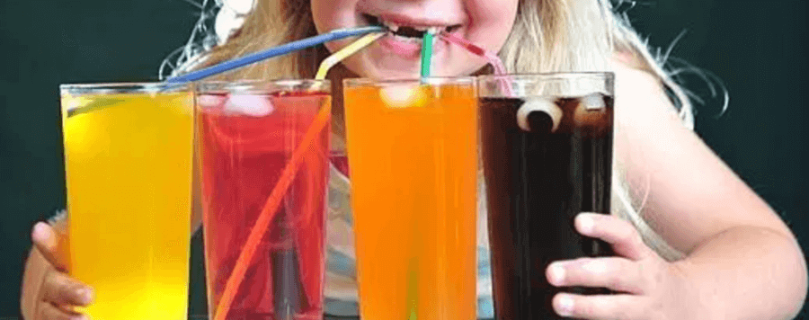 a blond haired little girl with missing front teeth drinking 4 different coloured drinks from 4 glasses with 4 different coloured straws. Blue straw in the yellow drink, yellow straw in the red drink, green straw in the orange drink and a red straw in the dark brown drink.